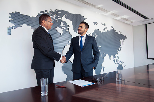 istock Businessmen shaking hands at conference table 1140459829