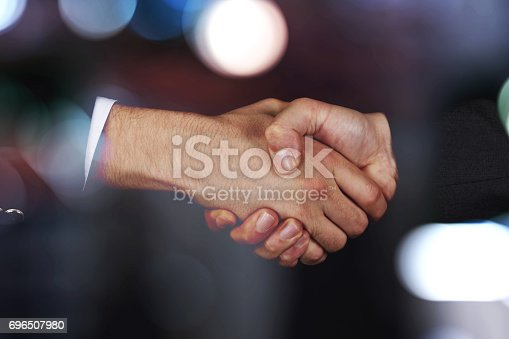 istock Businessmen shaking hands at the blurred background 696507980