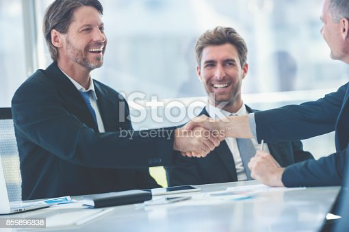 859896852istockphoto Businessmen shaking hands at the board room table. 859896838