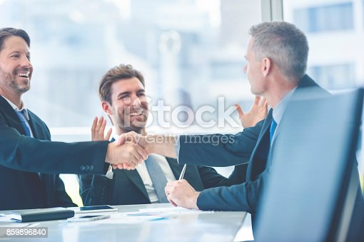 859896852istockphoto Businessmen shaking hands at the board room table. 859896840