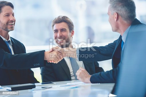 859896852istockphoto Businessmen shaking hands at the board room table. 859896842