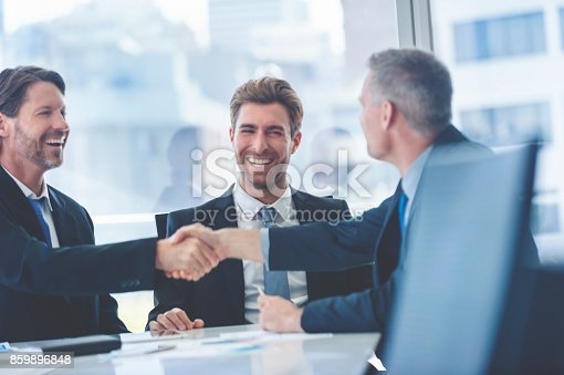 859896852istockphoto Businessmen shaking hands at the board room table. 859896848