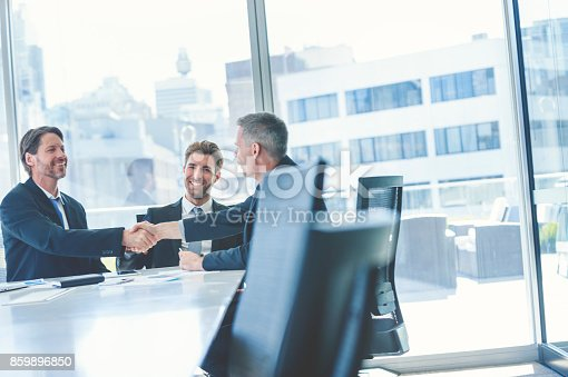 istock Businessmen shaking hands at the board room table. 859896850