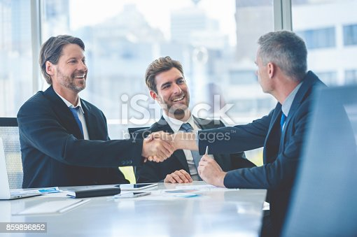Businessmen shaking hands at the board room table. They are all wearing suits, and they are smiling and happy. They have just sealed a contract