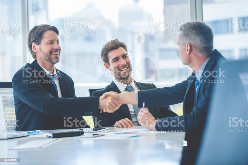 Businessmen shaking hands at the board room table. - foto stock