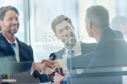 859896852istockphoto Businessmen shaking hands at the board room table 859896854