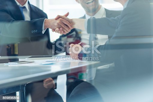 859896852istockphoto Businessmen shaking hands at the board room table. 859896856