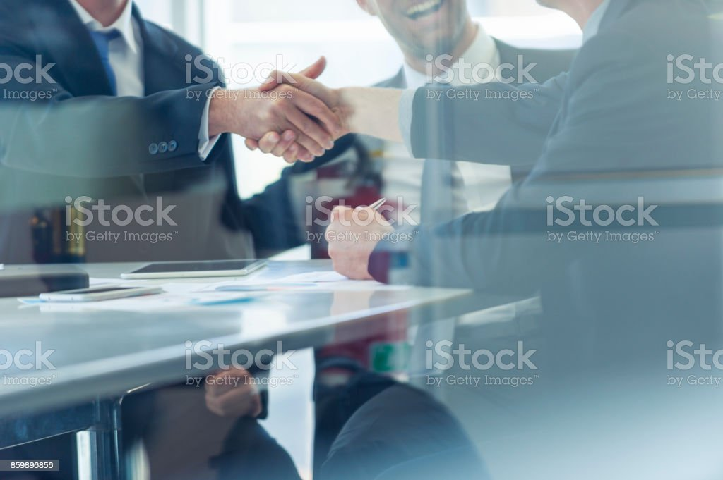Businessmen shaking hands at the board room table. stock photo