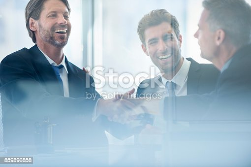 859896852istockphoto Businessmen shaking hands at the board room table 859896858