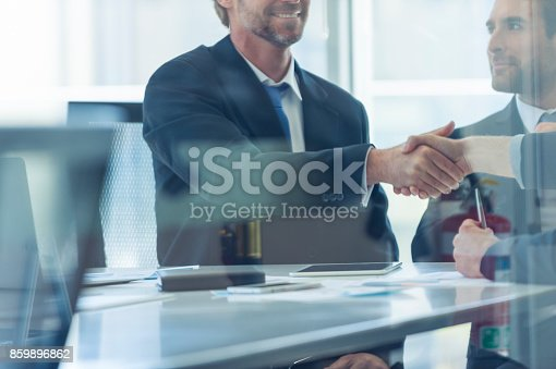 859896852istockphoto Businessmen shaking hands at the board room table. 859896862