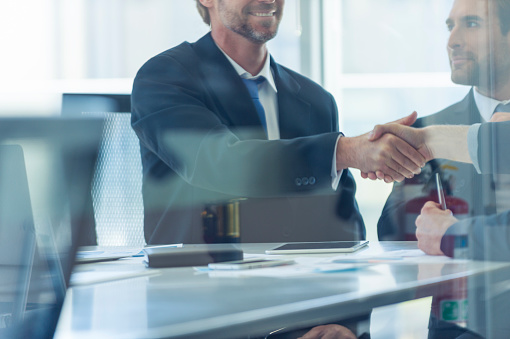 istock Businessmen shaking hands at the board room table. 859896862