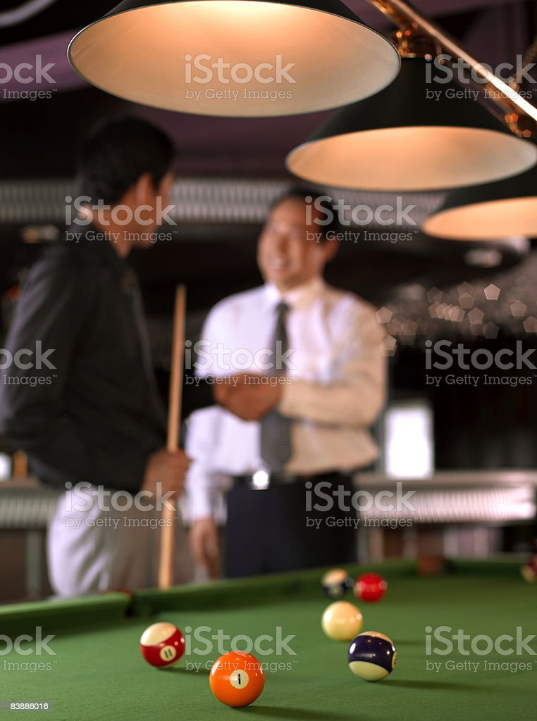 Businessmen shaking hands beside pool table royaltyfri bildbanksbilder