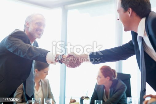 istock Businessmen shaking hands in conference room 147205264