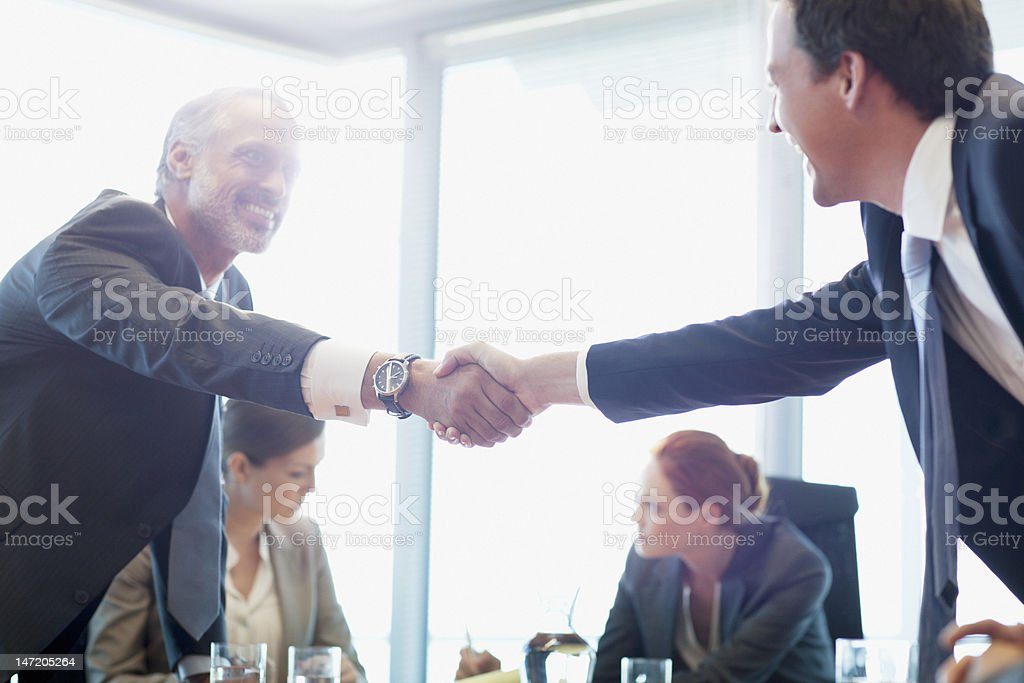 Businessmen shaking hands in conference room stock photo