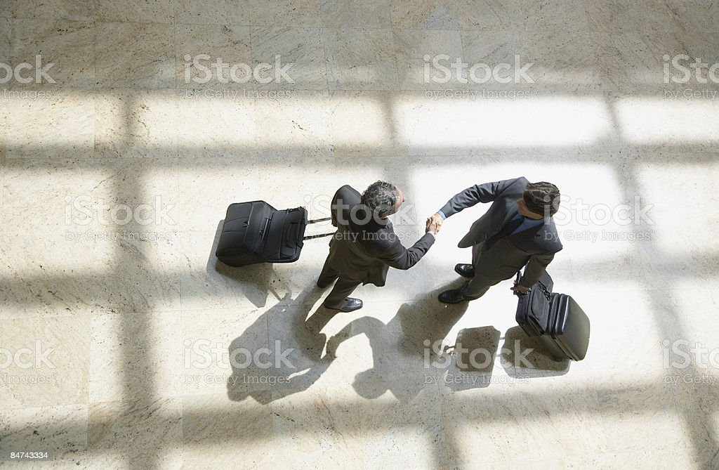Businessmen shaking hands in lobby royalty-free stock photo
