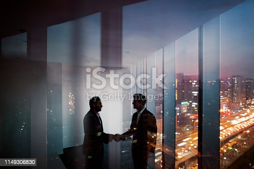 istock Businessmen shaking hands in office at night 1149306830