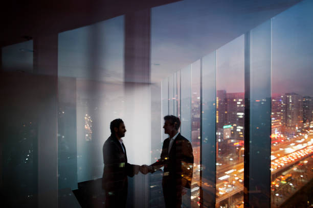 Businessmen shaking hands in office at night stock photo