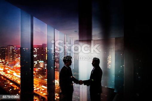 istock Businessmen shaking hands in office at night with city view 637945960