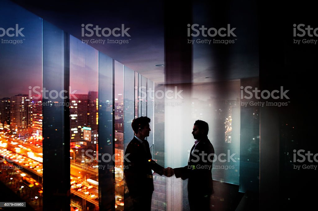 Businessmen shaking hands in office at night with city view – Foto
