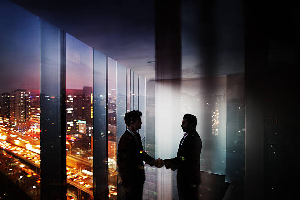 Businessmen shaking hands in office at night with city view - Photo