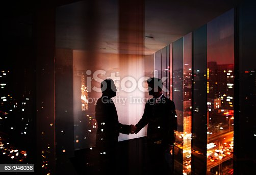 istock Businessmen shaking hands in office at night with city view 637946036