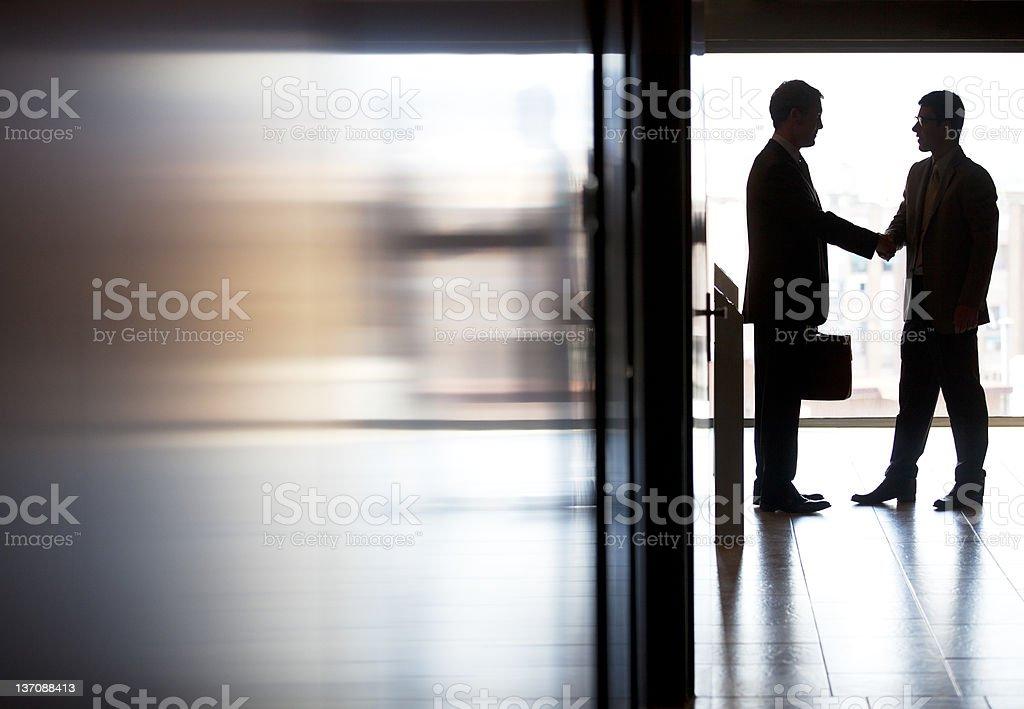 Businessmen shaking hands in office foto