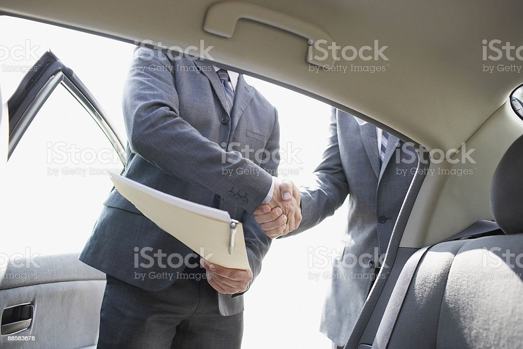 Businessmen shaking hands near car royalty-free stock photo