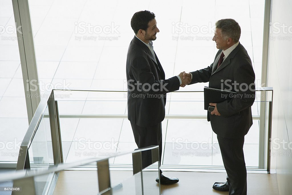 Businessmen shaking hands on stair landing royalty-free stock photo