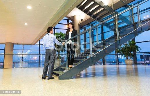 Businessmen shaking hands on steps before meeting.