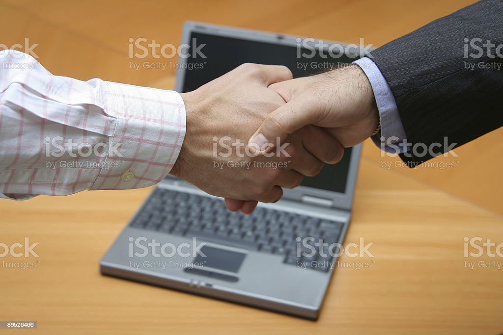 Businessmen shaking hands over a laptop royalty-free stock photo