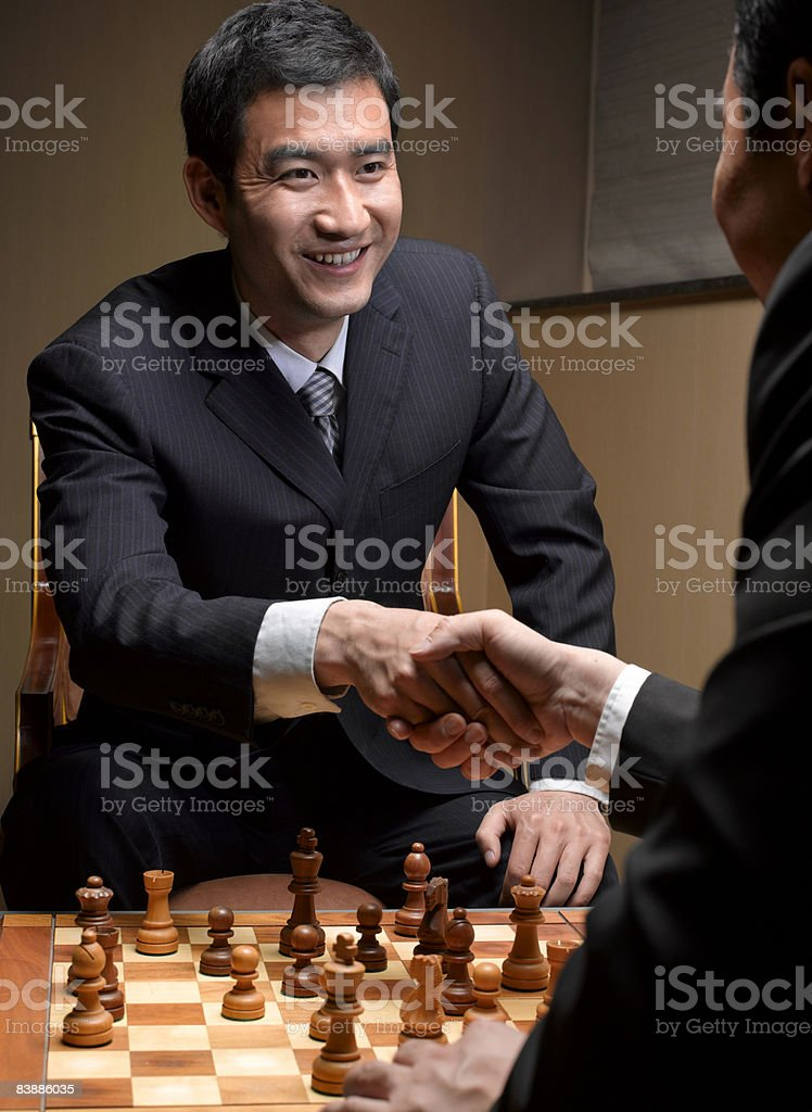 Businessmen shaking hands over chess board. royalty-free stock photo
