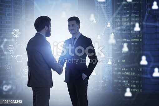 Two young businessmen shaking hands in night city with double exposure of blurry social network interface. Concept of hiring. Toned image