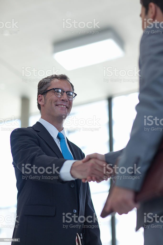 Businessmen shaking hands together royalty-free stock photo