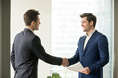 Handsome businessman handshaking with company coworker or partner at meeting, employer welcoming job candidate before interview. Business etiquette, entrepreneurs partnership, making successful deal