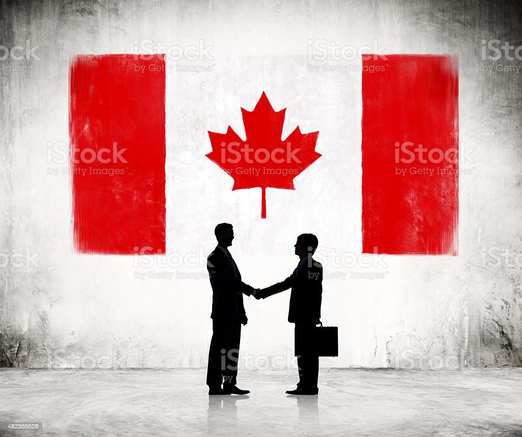 Businessmen Shaking Hands with Canadian Flag stock photo