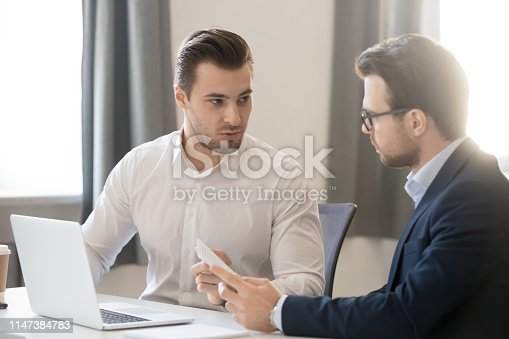 Serious caucasian colleagues talking discuss project in office, manager explains new idea to teammate, businessmen disputing brainstorming together sitting at desk, teamwork help cooperation concept