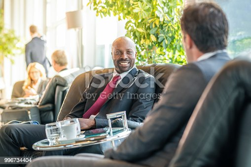 Businessmen sitting on chair at airport departure area.
