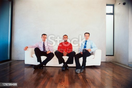 530281723istockphoto Businessmen sitting on couch in office 129299499