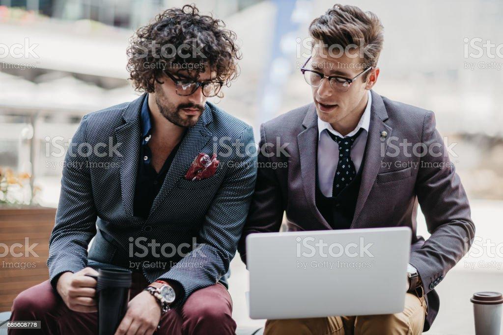 坐在長椅上,使用筆記本電腦的商人 免版稅 stock photo