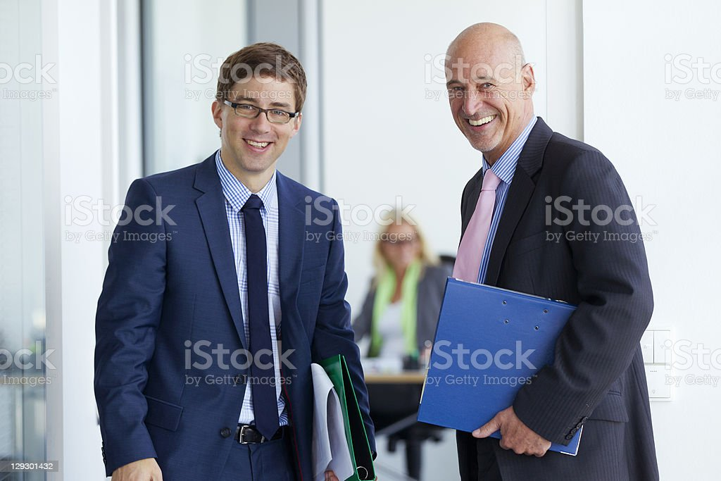 Businessmen smiling in office stock photo