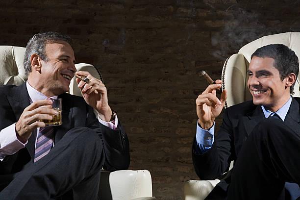 businessmen smoking cigars - guy with cigar stockfoto's en -beelden