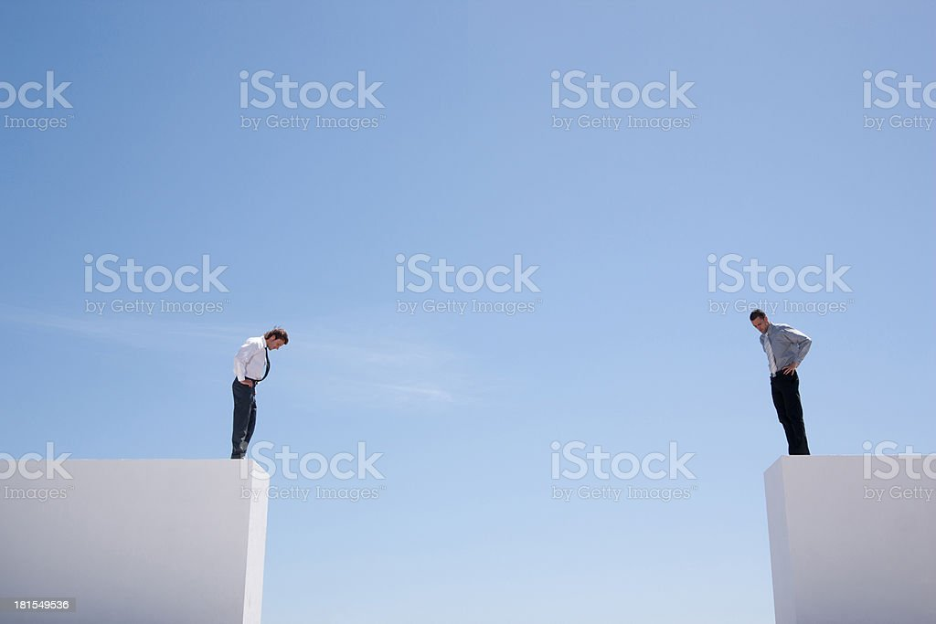 Businessmen standing on wall looking down  stock photo