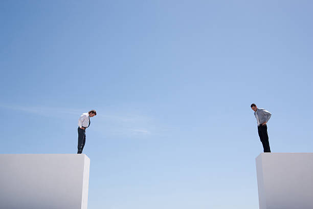 businessmen standing on wall looking down  - separation stock photos and pictures