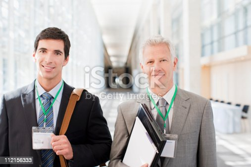 istock Businessmen standing together in office 112156333