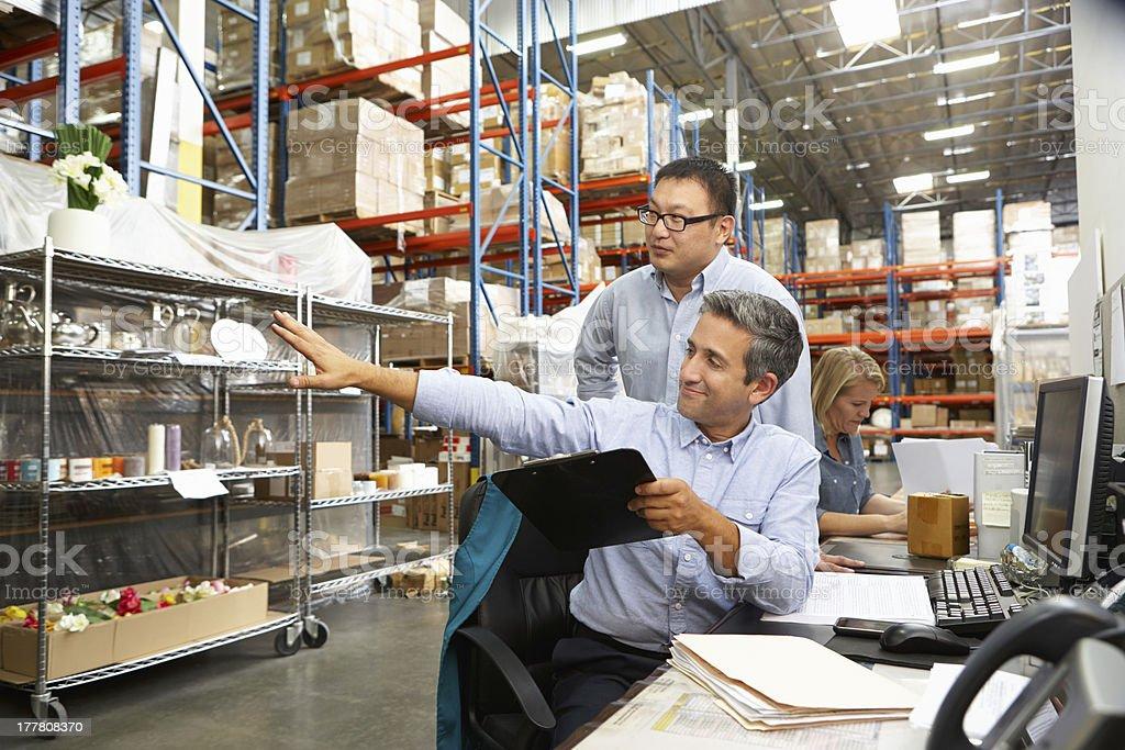 2 businessmen staring at some warehouse racking stock photo