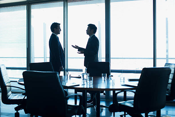 Businessmen talking face to face in conference room stock photo