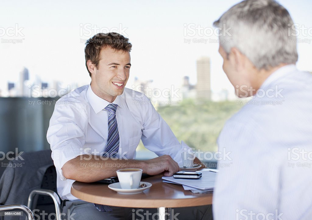 Businessmen talking in cafe royalty free stockfoto