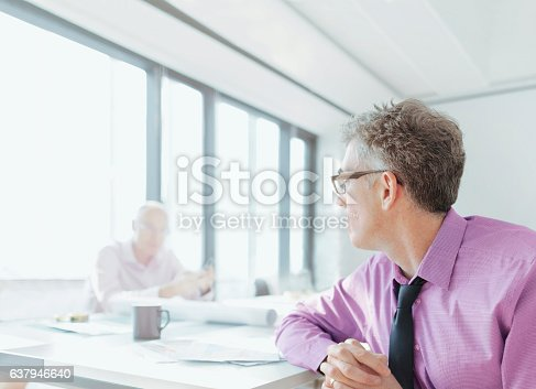 Businessmen talking in meeting room with design documents on table