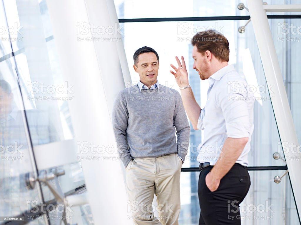 businessmen talking in modern office stock photo