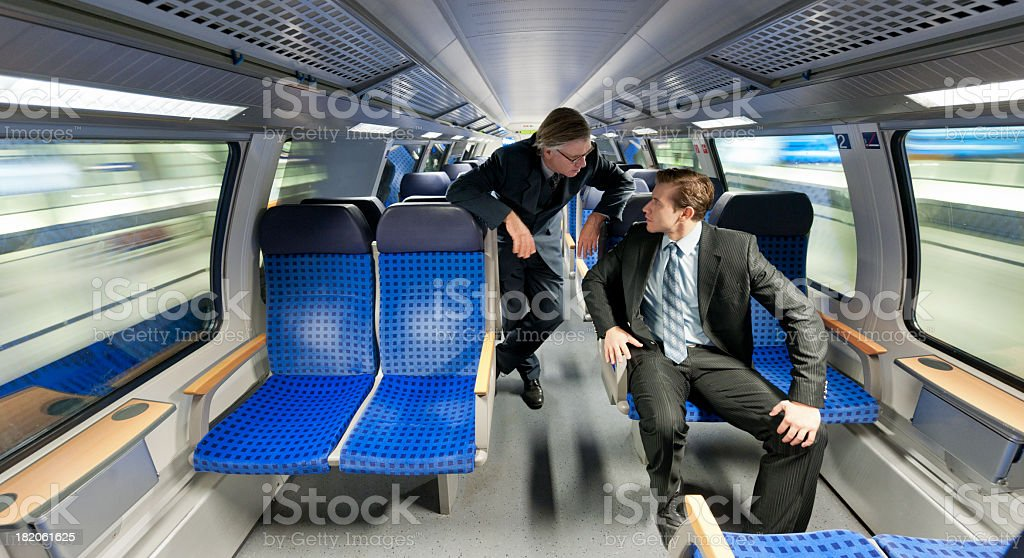 businessmen talking in moving train stock photo